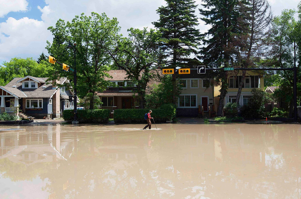 . A woman walks down a flooded street in the Elbow Park area of Calgary, Alberta June 22, 2013.REUTERS/Todd Korol