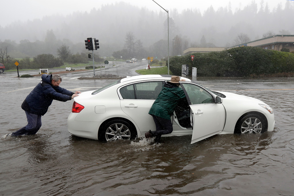 . Terry Howard, left, pushes his stalled car from a flooded street with the help of his wife Janie Tuesday, Feb. 7, 2017, in Felton, Calif. Flash flood watches are in place for parts of Northern California down through the Central Coast as heavy rains swamp roads and threaten to overtop rivers and creeks. (AP Photo/Marcio Jose Sanchez)