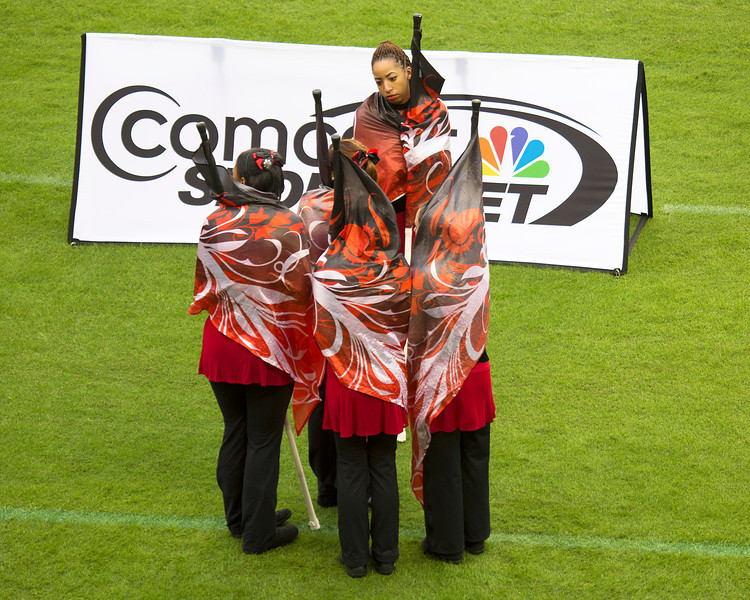 A dance team group is cold.  They wrap up in their flags.