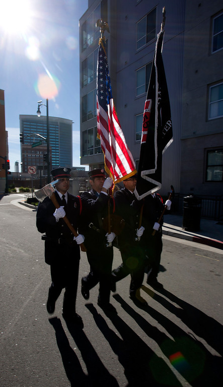 """. An Oakland Fire Department color guard preceeds a fire truck bearing a fragment of steel from the twin towers of the World Trade Center, at a ceremony to dedicate the final section of \""""Remember Them,\"""" artist Mario Chiodo\'s paean to heroes of civil rights and humanity, Thursday, Feb. 21, 2013 in Oakland Calif. (D. Ross Cameron/Staff)"""
