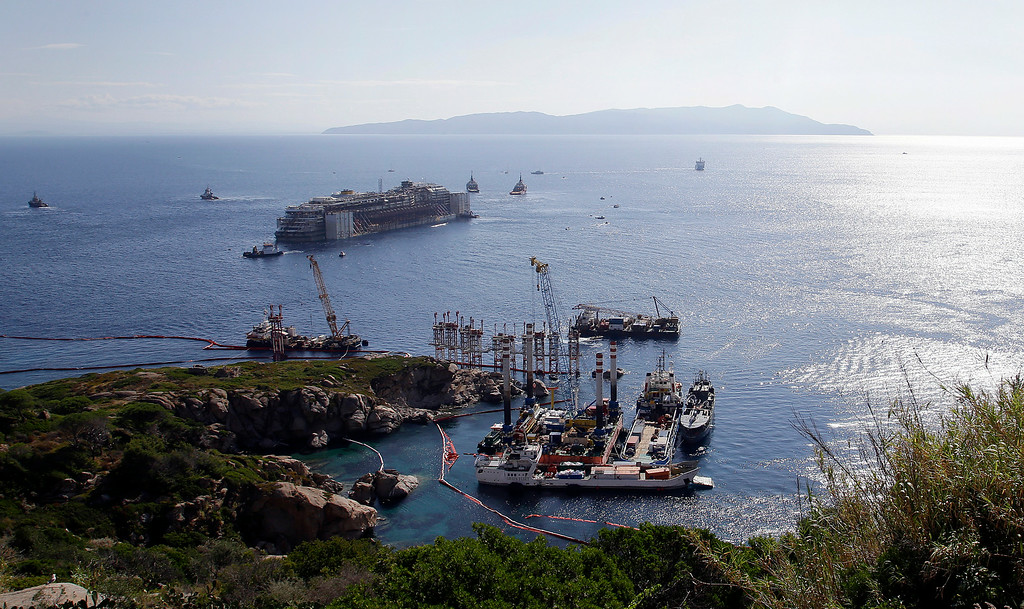 . The Costa Concordia cruise wreck is towed away from the tiny Tuscan island of Isola del Giglio, Italy, Wednesday, July 23, 2014.  After more than two years since it slammed into a reef along the coastline of Isola del Giglio the wreck has begun its last journey, to the Italian port of Genoa, where it will be scrapped. 32 people died in the incident. (AP Photo/Gregorio Borgia)