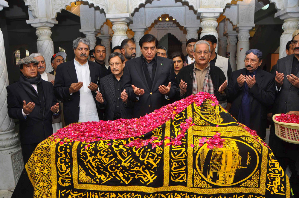 Description of . Former Governor of Punjab Latif Khosa (L), Pakistan's Defence Minister Naveed Qamar (2nd L), Justice Minister Farooq Naek (3rd L), Prime Minister Raja Pervez Ashraf (4th L), Chief Minister of Sindh Syed Qaim Ali Shah (2nd R) pray near the grave of former Prime Minister Benazir Bhutto during her death anniversary at the Bhutto family mausoleum in Garhi Khuda Bakhsh, near Larkana December December 27, 2012. Bhutto was killed in a gun and suicide bomb attack after an election rally in the city of Rawalpindi on December 27, 2007, weeks after she returned to Pakistan after years in self-imposed exile. REUTERS/Nadeem Soomro