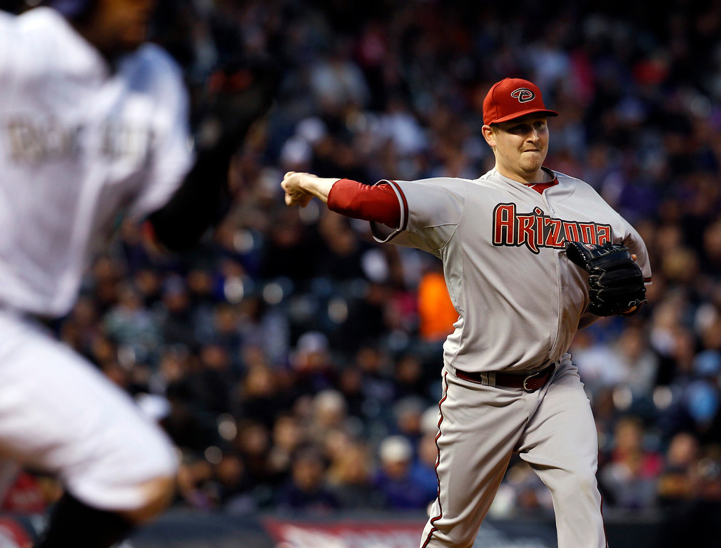 . Arizona Diamondbacks starting pitcher Trevor Cahill, right, turns after fielding a ground ball to throw out Colorado Rockies\' Eric Young Jr. in the fifth inning of a baseball game in Denver, Saturday, April 20, 2013. (AP Photo/David Zalubowski)