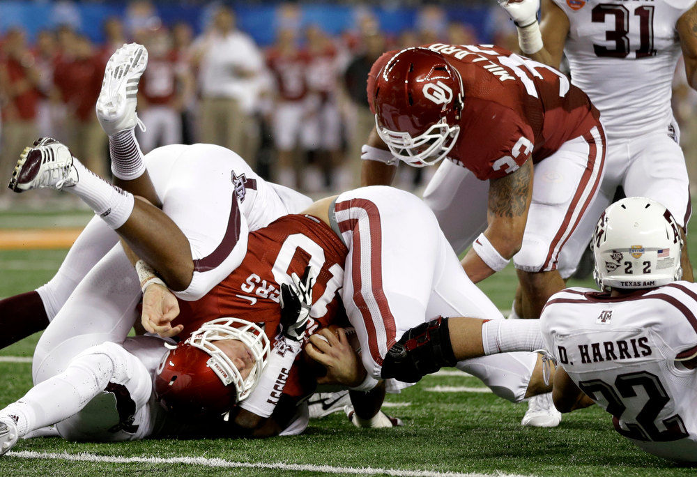 Description of . Oklahoma quarterback Blake Bell is stopped short of the goal line by Texas A&M defenders as A&M's Dustin Harris (22) and Oklahoma's Trey Millard (33) watch in the first half of the Cotton Bowl NCAA college football game Friday, Jan. 4, 2013, in Arlington, Texas. (AP Photo/Tony Gutierrez)