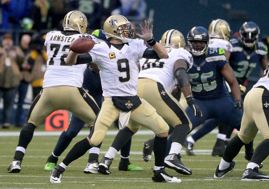 . SEATTLE, WA - JANUARY 11:  Quarterback Drew Brees #9 of the New Orleans Saints throws the ball in the second half against the Seattle Seahawks during the NFC Divisional Playoff Game at CenturyLink Field on January 11, 2014 in Seattle, Washington.  (Photo by Harry How/Getty Images)