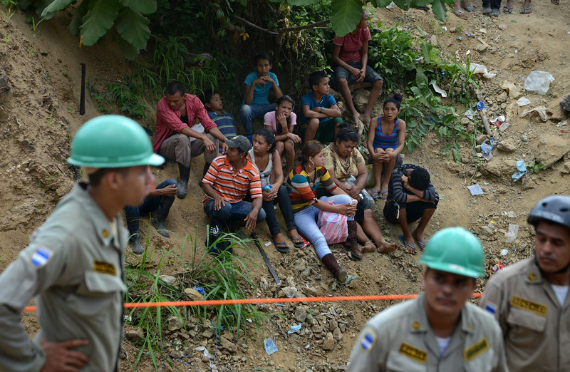 ". People wait (background) as firefighters and rescuers try to reach the at least 11 miners trapped inside the San Juan mine, in the Honduran southern department of Choluteca, on July 3, 2014 a day after the gold mine collapsed. Rescuers in Honduras said there were signs of life Thursday from within the mine as they intensified efforts to save them. Using sound detection equipment lowered into the unlicensed mine, ""we\'ve received signals, sounds in the part of the mine where the workers are trapped,\"" Moises Alvarado, head of the national emergency authority, told local radio. The cave-in on Wednesday struck the mine at a depth of 80 meters (260 feet) near the southern town of El Corpus. Rescuers cannot use machinery to try to get to the miners because the ground is unstable. (ORLANDO SIERRA/AFP/Getty Images)"