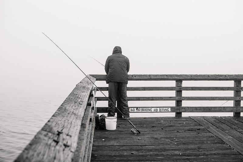 A fisherman on a dock during a foggy morning at Alki Beach