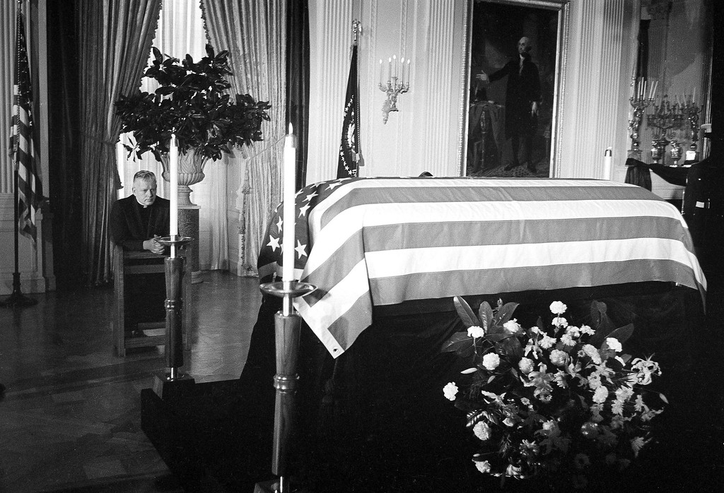 . A Roman Catholic priest kneels in prayer beside the  coffin bearing Kennedy\'s body Nov. 23, 1963, in the  East Room of the White House. Associated Press file
