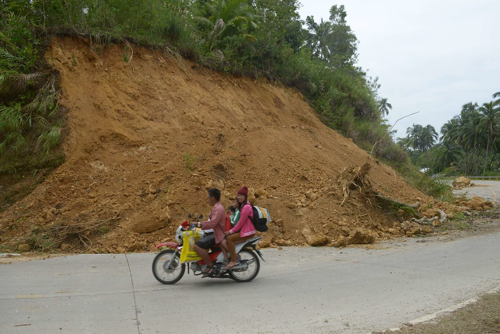 . Residents pass by a landslide area on the popular tourist island of Bohol, central Philippines on October 16, 2013 following a 7.1-magnitude earthquake in the area on October 15.  AFP PHOTO / Jay DIRECTO/AFP/Getty Images