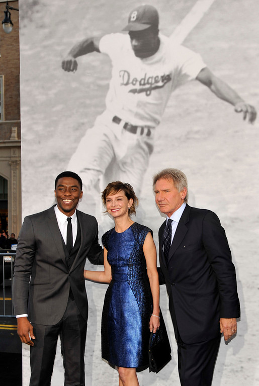 ". Chadwick Boseman, left, who plays baseball legend Jackie Robinson in ""42,\"" poses with fellow cast member Harrison Ford and his wife Calista Flockhart at the Los Angeles premiere of the film at the TCL Chinese Theater on Tuesday, April 9, 2013 in Los Angeles. (Photo by Chris Pizzello/Invision/AP)"