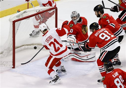 . Detroit Red Wings left wing Tomas Tatar (21) scores past Chicago Blackhawks goalie Corey Crawford (50) as Brent Seabrook (7), Brad Richards (91) and Patrick Kane (88) watch during the second period of an NHL hockey game Wednesday, Feb. 18, 2015, in Chicago. (AP Photo/Charles Rex Arbogast)