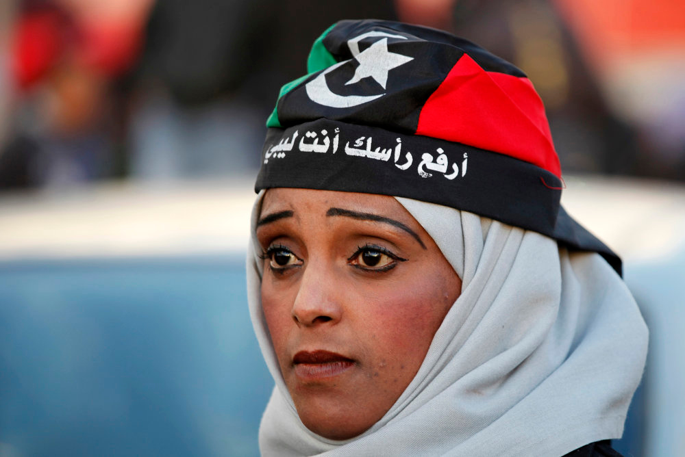 Description of . A Libyan woman wearing a depiction of the national flag bearing the words,