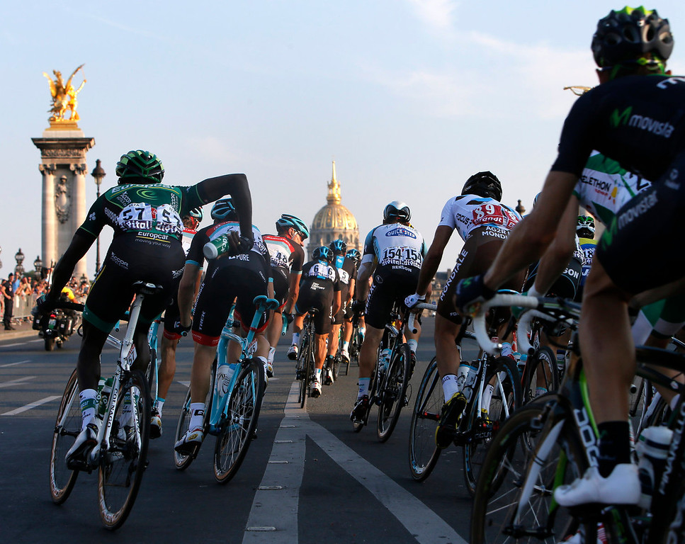 . Forty-two-year-old Jens Voigt of Germany, center with number 48, passes Alexandre III bridge with the pack as Dome des Invalides is seen in the background during the 21st and last stage of the 100th edition of the Tour de France cycling race over 133.5 kilometers (83.4 miles) with start in Versailles and finish in Paris, France, Sunday July 21 2013. (AP Photo/Laurent Rebours)
