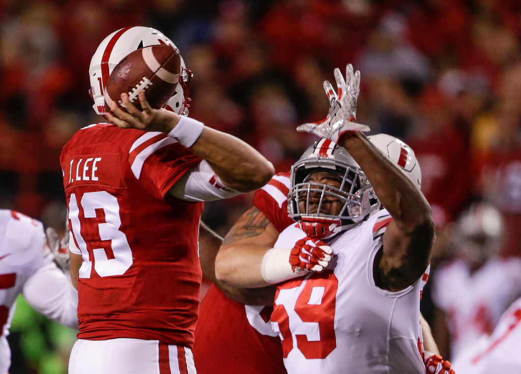 . Nebraska quarterback Tanner Lee (13) throws under pressure from Ohio State defensive lineman Tyquan Lewis (59) during the first half of an NCAA college football game in Lincoln, Neb., Saturday, Oct. 14, 2017. (AP Photo/Nati Harnik)
