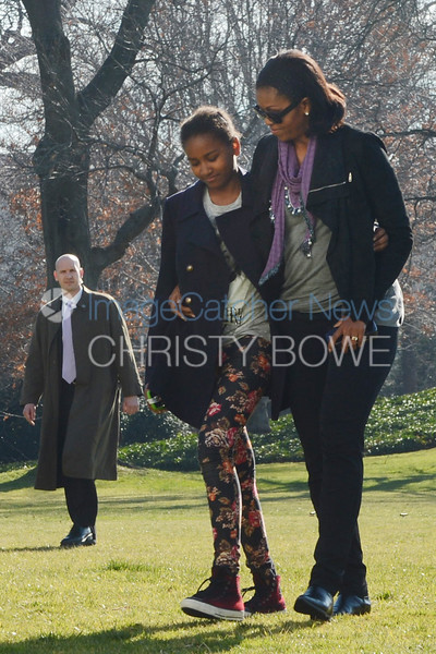 First Lady Michelle and daughter Sasha walk to the Residence as a Secret Service Agent looks on.