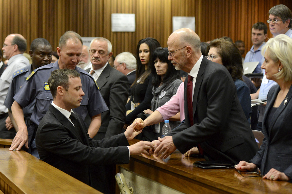. Oscar Pistorius, front left, greets his uncle Arnold Pistorius, right, and other family members as he is led out of court in Pretoria, South Africa, Tuesday, Oct. 21, 2014. (AP Photo/Herman Verwey, Pool)