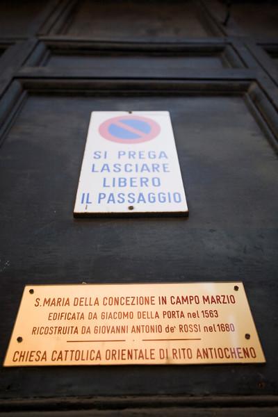 Traffic and information signs on the door of Santa Maria della Concezione in Campo Marzio church, Rome