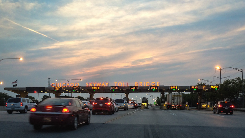 Cars approach the Chicago Skyway toll plaza at dusk