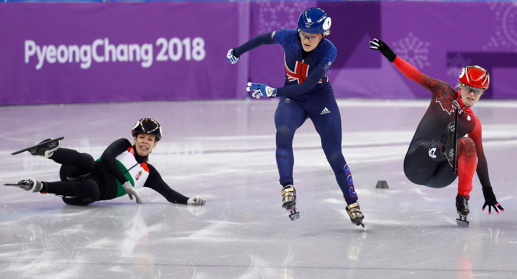 . Elise Christie, centre, of Britain skates as Andrea Keszler, left, of Hungary and Kim Boutin, right, of Canada fall during the ladies\' 500 meters short track speedskating quarterfinal in the Gangneung Ice Arena at the 2018 Winter Olympics in Gangneung, South Korea, Tuesday, Feb. 13, 2018. (AP Photo/Patrick Semansky)
