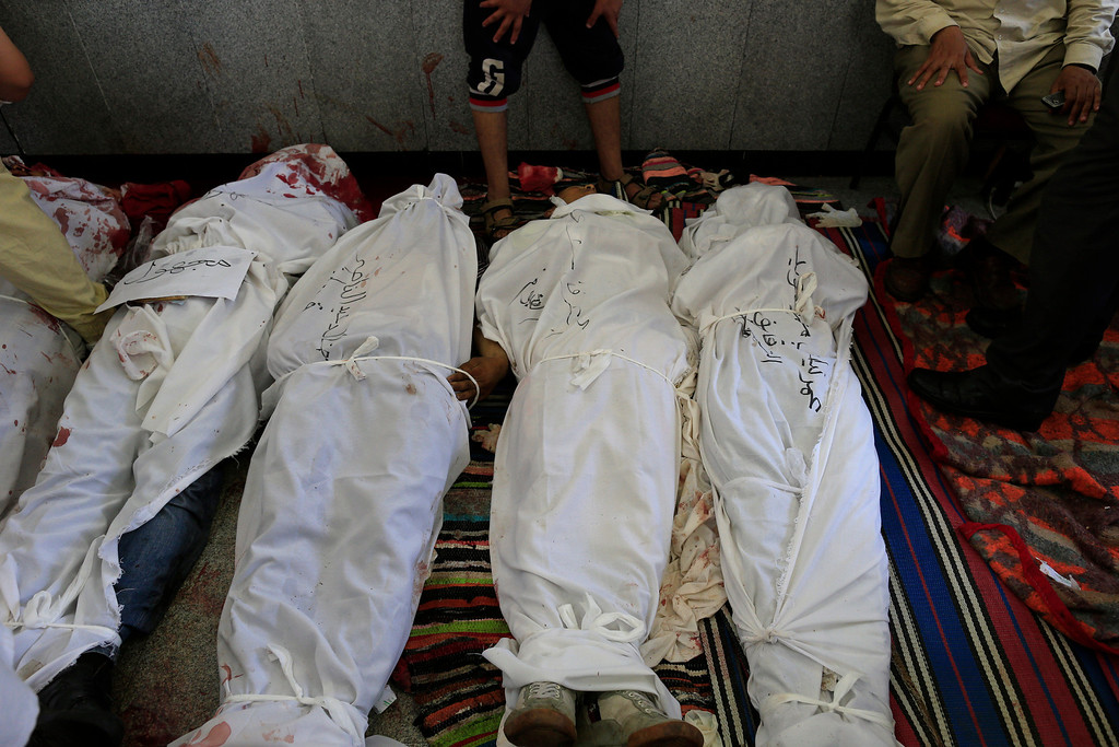 . Egyptians identify bodies of supporters for Egypt\'s ousted President Mohammed Morsi after they were killed in clashes with security forces at Nasr City, where pro-Morsi protesters have held a weeks-long sit-in, in a field hospital in Cairo, Egypt, Saturday, July 27, 2013. Overnight clashes between security forces and supporters of ousted Egyptian President Mohammed Morsi in east Cairo left scores of protesters dead and hundreds injured following a day of massive pro-military rallies backing a tough hand against Morsiís backers and the Muslim Brotherhood group from which he hails. (AP Photo/Hassan Ammar)