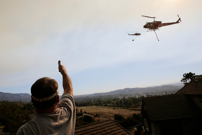 . Fred Garside gives a thumb up toward helicopters carrying over on Thursday, Jan. 16, 2014, in Azusa, Calif. A wildfire burned out of control near homes in the dangerously dry foothills of the San Gabriel Mountains early Thursday, fanned by gusty Santa Ana winds that spit embers into neighborhoods in the city below, igniting trees. Evacuations were ordered for houses at the edge of the fire. (AP Photo/Jae C. Hong)