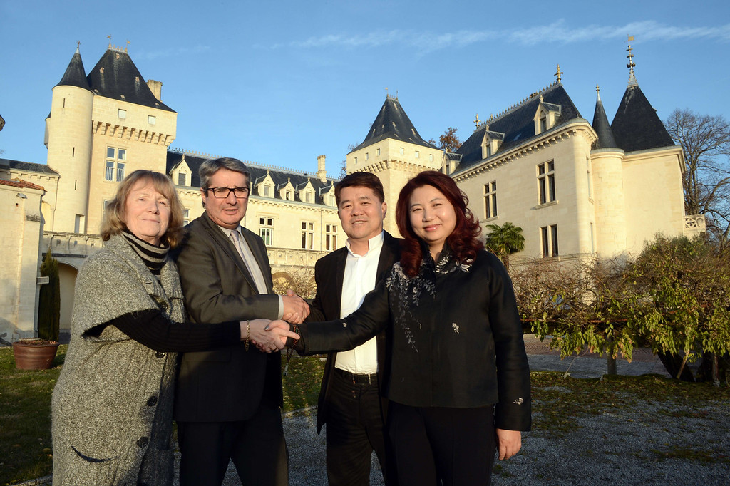 . Chinese billionaire Lam Kok (2nd R) and his spouse pose alongside the French former owner of the Chateau de La Riviere, James Gregoire (2nd L), and his spouse in front of the castle in La Riviere, on December 20, 2013. The deal which was concluded on December 19 for Chinese billionaire Lam Kok to buy a Bordeaux vineyard, le Château de La Rivière, turned to tragedy today after the helicopter which the billionaire and the vineyard\'s French former owner James Gregoire were using to fly over the property crashed into the Dordogne river. This photograph was taken less than an hour before the crash. The French former owner of the vineyard James Gregoire, the new Chinese buyer Lam Kok, and Lam Kok\'s 12-year-old son are still missing. AFP PHOTO / MEHDI  FEDOUACH/AFP/Getty Images