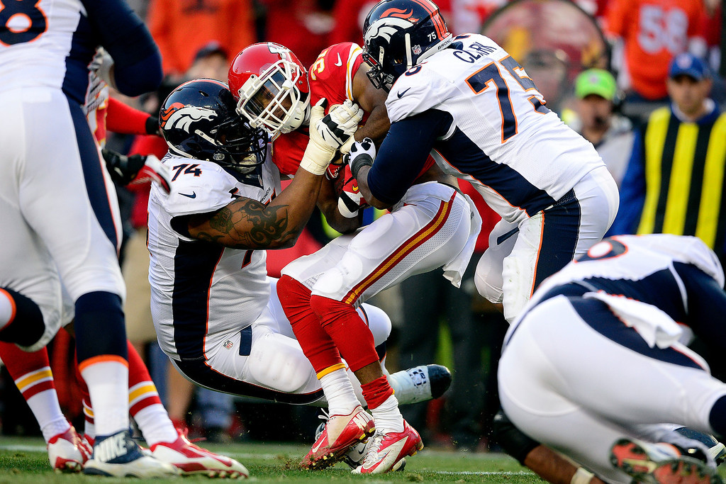 . Chris Clark (75) of the Denver Broncos and Orlando Franklin (74)tackle Marcus Cooper (31) of the Kansas City Chiefs after he intercepted a pass by Peyton Manning (18)during the first half of action at Arrowhead Stadium.  (Photo by AAron Ontiveroz/The Denver Post)