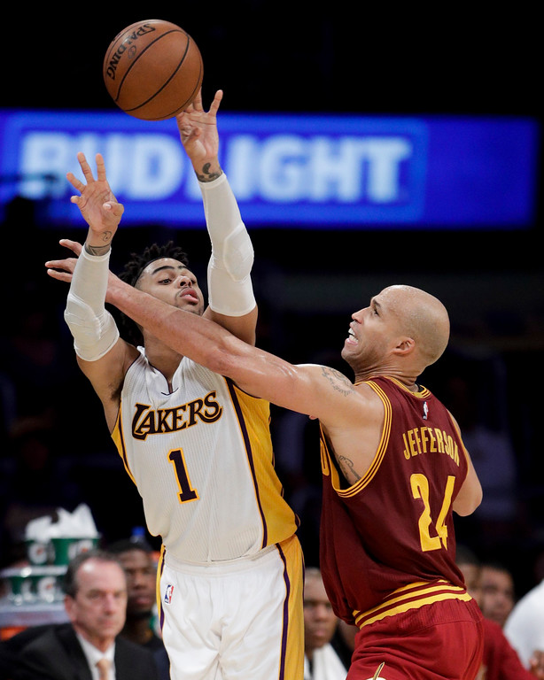 . Los Angeles Lakers\' D\'Angelo Russell, left, passes the ball under defense by Cleveland Cavaliers\' Richard Jefferson during the second half of an NBA basketball game Sunday, March 19, 2017, in Los Angeles. The Cavaliers won 125-120. (AP Photo/Jae C. Hong)