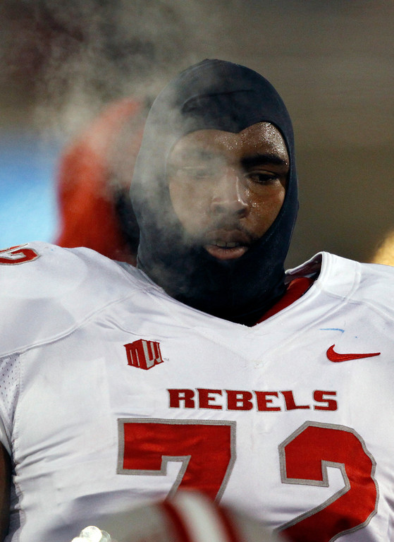 . Steam rises from UNLV offensive lineman Ron Scoggins as he waits on the sidelines to take the field against Air Force in the first quarter of an NCAA football game at Air Force Academy, Colo., on Thursday, Nov. 21, 2013. (AP Photo/David Zalubowski)