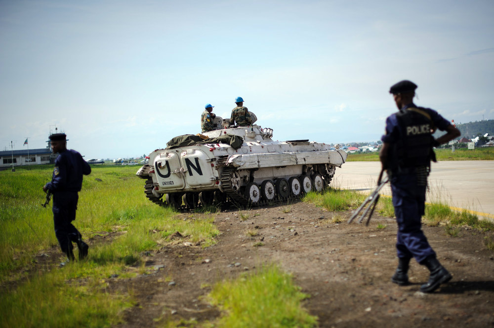 . Congolese government policemen walk on December 4, 2012 alongside the runway near to a United Nations armoured personnel carrier at the airport in Goma, eastern Democratic Republic of the Congo, during a visit by Congo\'s interior minister. The airport was held by United Nations forces whilst M23 overran the city two weeks ago, before leaving on December 1. Government troops returned to the city on December 3. PHIL MOORE/AFP/Getty Images