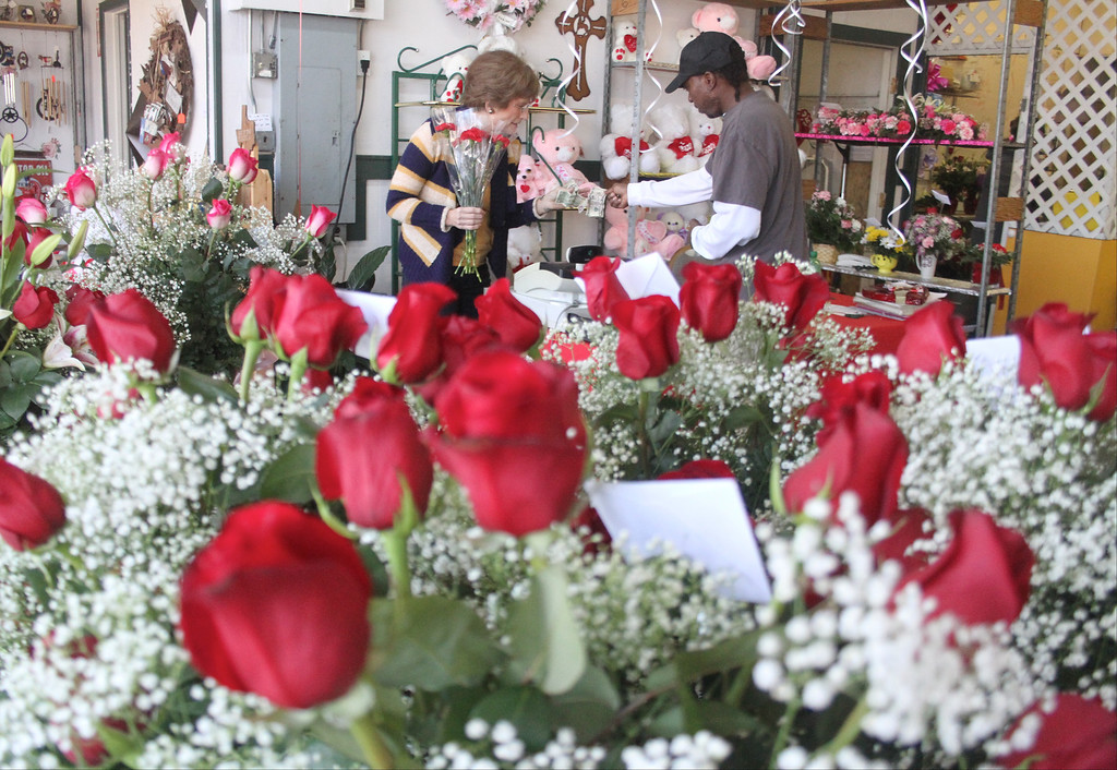 . Wanda Smith, left, gives Clarence Coleman a bouquet of red roses he ordered for Valentine\'s Day at Flowers Texas Style on Thursday, Feb. 14, 2013, in Conroe, Texas. Workers at the shop estimate they will have assembled more than 700 arrangements before the end of Valentine\'s Day. (AP Photo/ The Courier, Jason Fochtman)