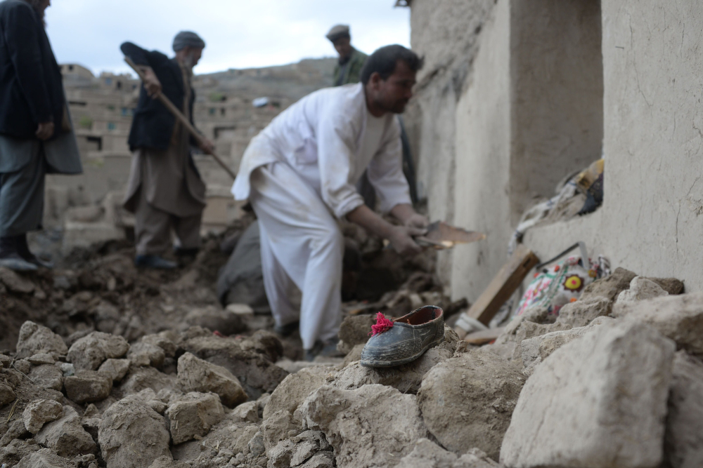 . A piece of footwear is pictured as rescuers search for survivors trapped under the mud in Argo district of Badakhshan province on May 3, 2014 after a massive landslide May 2 buried a village. Rescuers searched in vain for survivors May 3 after a landslide buried an Afghan village, killing 350 people and leaving thousands of others feared dead amid warnings that more earth could sweep down the hillside. Local people made desperate efforts to find victims trapped under a massive river of mud that engulfed Aab Bareek village in Badakhshan province, where little sign remained of hundreds of destroyed homes. (FARSHAD USYAN/AFP/Getty Images)