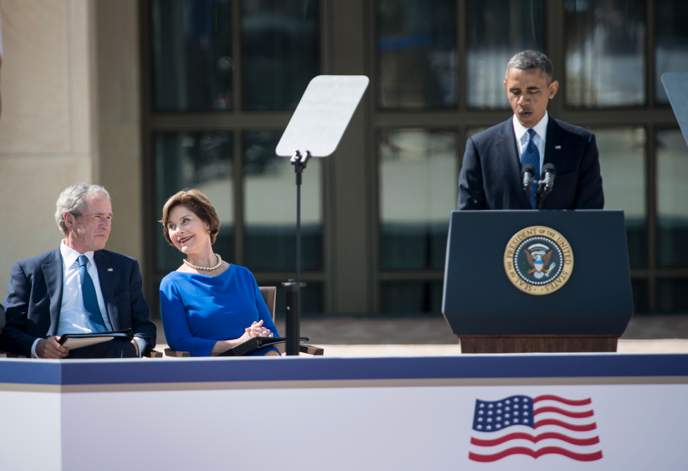 Description of . Former US President George W. Bush and Laura Bush listen while US President Barack Obama speaks during a dedication ceremony at the George W. Bush Library and Museum on the grounds of Southern Methodist University April 25, 2013 in Dallas, Texas.  BRENDAN SMIALOWSKI/AFP/Getty Images