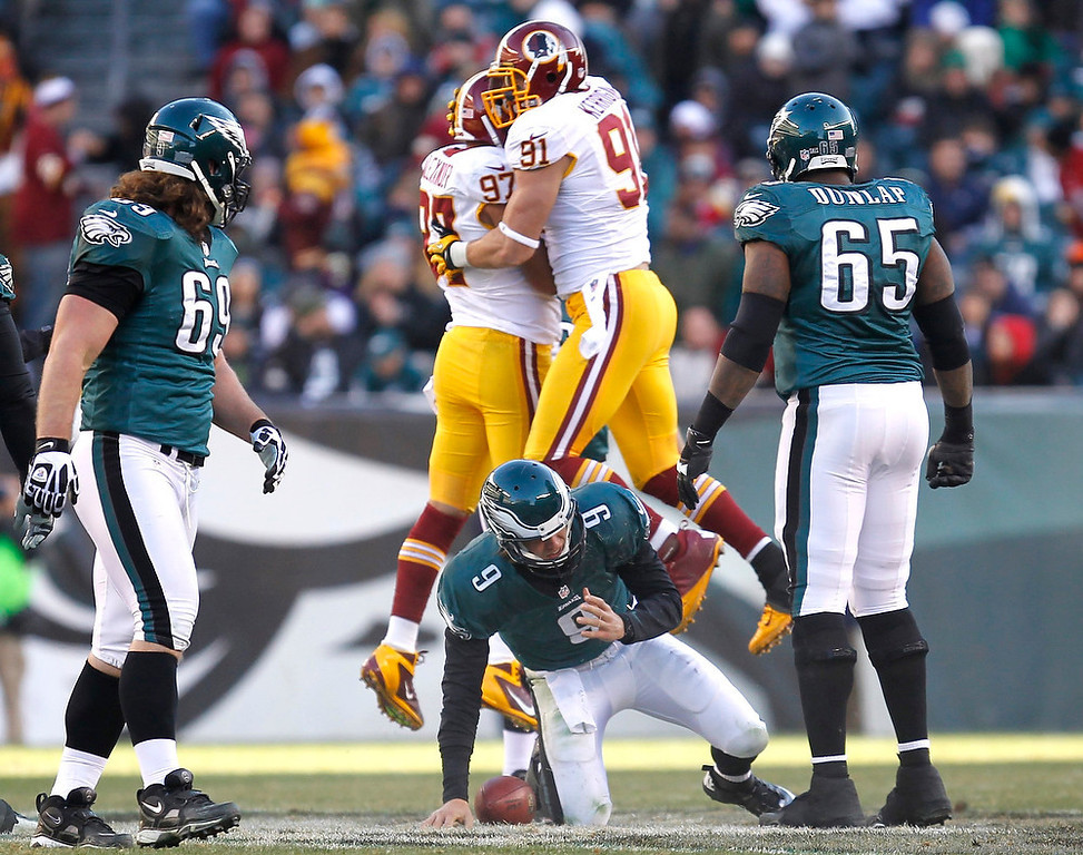 . Philadelphia Eagles quarterback Nick Foles (9) is slow getting up after a sack as Washington Redskins defenders Lorenzo Alexander (97) and Ryan Kerrigan (91) celebrate during the third quarter of their NFL football game in Philadelphia, Pennsylvania December 23, 2012. REUTERS/Tim Shaffer