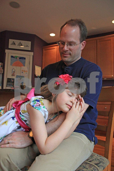 Young daughter finds comfort in her father's arms.