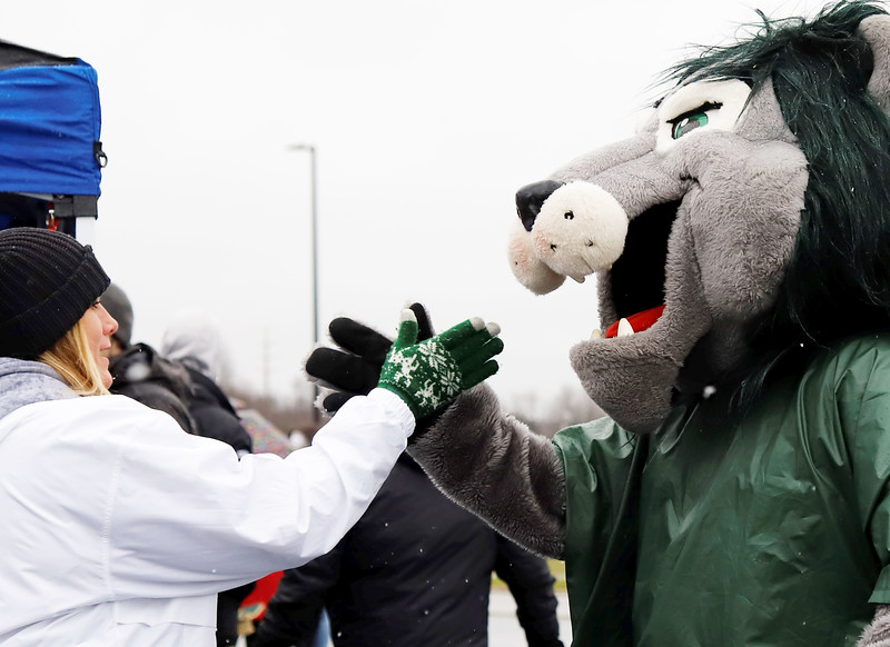 Melissa Holtz, mother of Slippery Rock defensive back Dalton Holt, high fives SRU mascot Rocky while he was making his rounds at pregame tailgates Saturday. Seb Foltz/Butler Eagle
