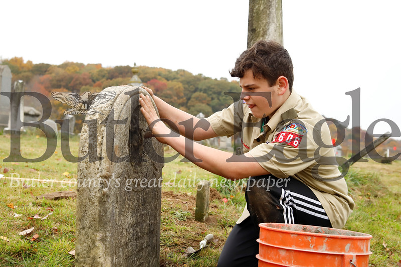 Tyler Rasmussen, 13, brushes off dirt from a tombstone in the the Harmony Mennonite Meetinghouse  Cemetery. Rasmussen and three other scouts from Boy Scout Troup 1606 worked on fixing up the cemetary for their Eagle Scout projects. Seb Foltz/Butler Eagle