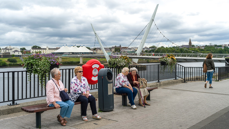 Tourists resting on benches on sidewalk, The Peace Bridge, Londonderry, Northern Ireland, United Kingdom