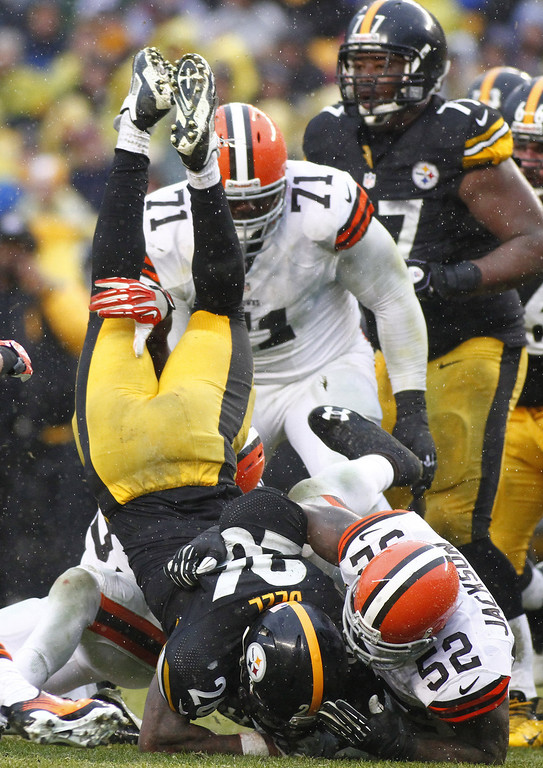 . Le\'Veon Bell #26 of the Pittsburgh Steelers is up ended while rushing against the Cleveland Browns during the game on December 29, 2013 at Heinz Field in Pittsburgh, Pennsylvania.  (Photo by Justin K. Aller/Getty Images)