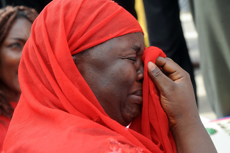 ". One of the mothers of the missing Chibok school girls wipes her tears as she cries during a rally by civil society groups pressing for the release of the girls in Abuja on May 6, 2014, ahead of World Economic Forum. Members of civil society groups marched through the streets of Abuja and to the Nigerian defence headquarters to meet with military chiefs, to press for the release of more than 200 Chibok school girls abducted three weeks ago. Suspected Boko Haram Islamists have kidnapped eight more girls from Nigeria\'s embattled northeast, residents said on May 6, after the extremist group\'s leader claimed responsibility for abducting more than 200 schoolgirls last month and said in a video he was holding them as ""slaves\"" and threatened to \""sell them in the market\"".  (PIUS UTOMI EKPEI/AFP/Getty Images)"