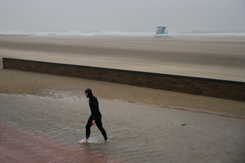 . A surfer walks through a flooded area on the beach Friday, Feb. 17, 2017, in Huntington Beach, Calif. A major Pacific storm has unleashed downpours and fierce gusts on Southern California, triggering flash flood warnings and other problems. (AP Photo/Jae C. Hong)