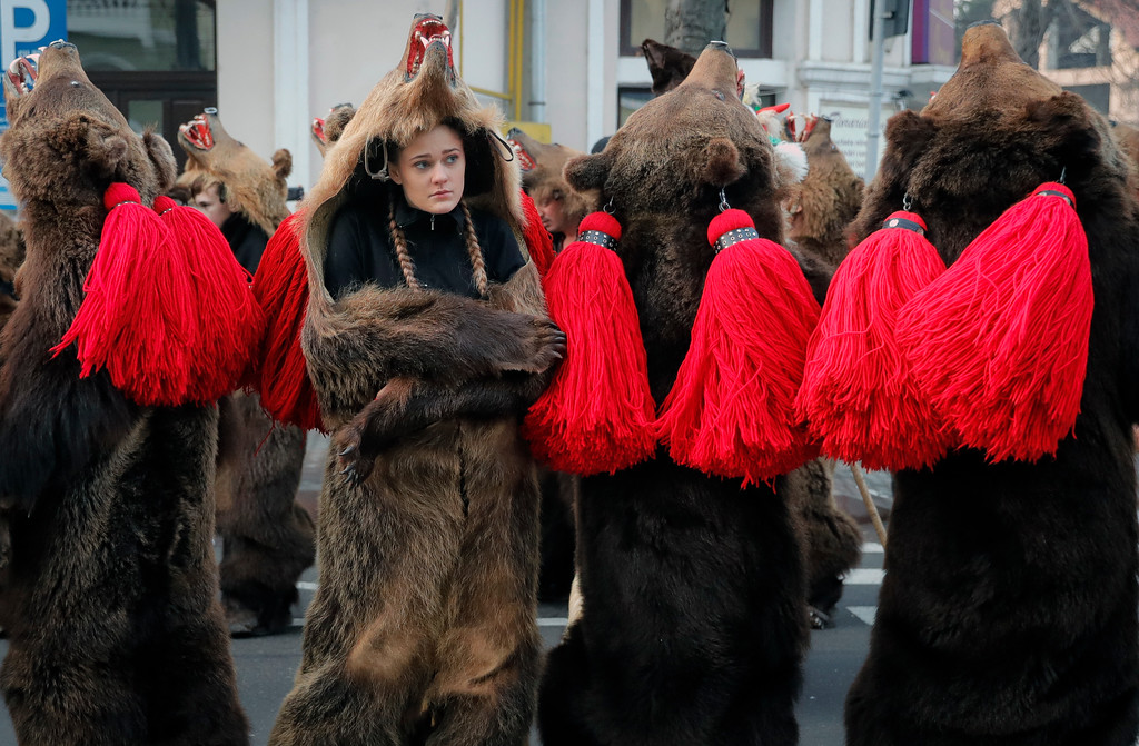 . Youngsters wearing bear costumes dance during an annual ritual in Piatra Neamt, northern Romania, Thursday, Dec. 28, 2017. The tradition, which originates in pre-Christian times when dancers wearing colored costumes or animal furs went from house to house in villages singing and dancing to ward off evil, has moved to Romania\'s cities, where dancers travel to perform the ritual for money.(AP Photo/Vadim Ghirda)