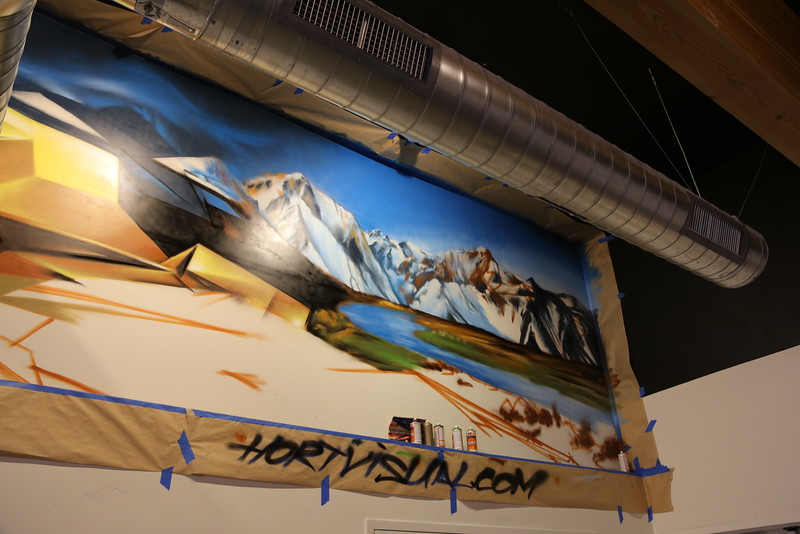John Horton spray paints a Sacramento mural on a wall in the Community Room. (Photo by Joan Cusick)