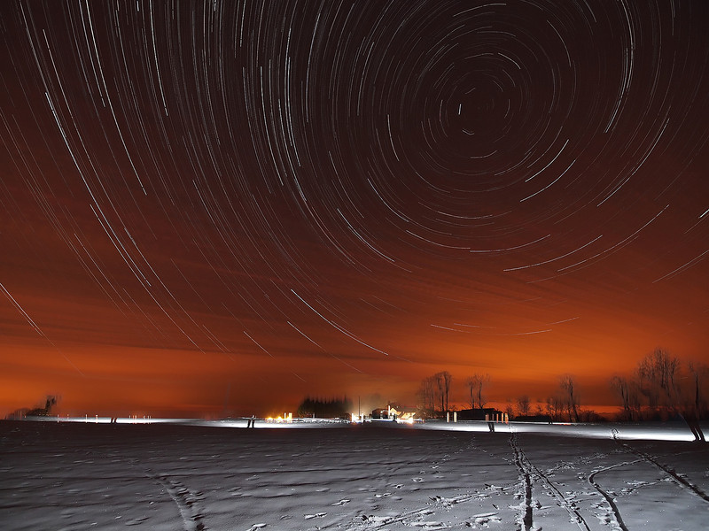 Feb 11 2012. First startrail of the winter with snow. Had a very small time window (6pm-9pm) before the cloud rolled in. Sat camera in a snow covered field, air temp -6C, with dew/heat shield preventing from freezing over. Shot 15s exposures continuous for 3 hrs at ISO 500, F4. Captured with Olympus E5 and 7-14mm. Flash bursts from me running all over field. Orange light pollution clearly visible, enhanced via clouds as they rolled in. Had a slight tripod wobble near end of shoot too which caused trail to slip slightly.