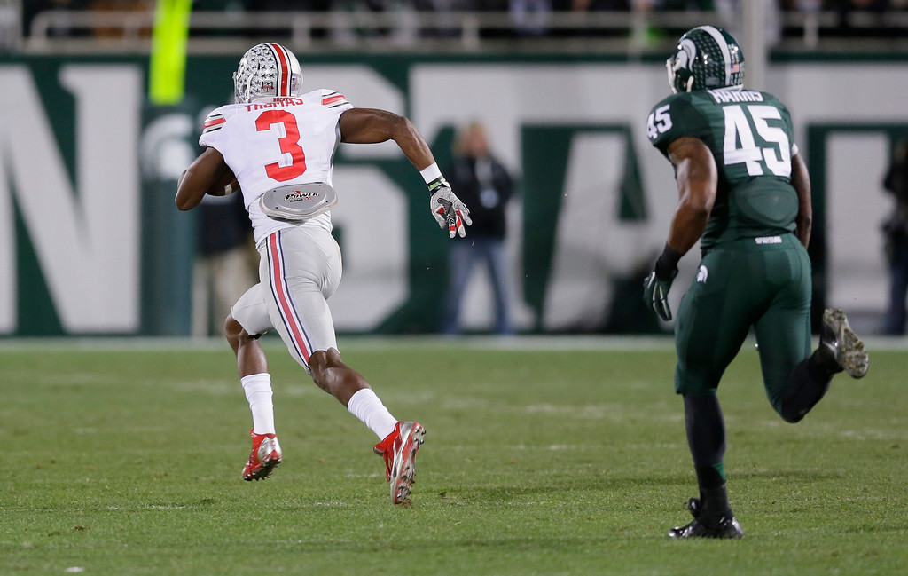 . Ohio State wide receiver Michael Thomas (3) breaks away from Michigan State linebacker Darien Harris (45) on a 79-yard touchdown run during the first half of an NCAA college football game in East Lansing, Mich., Saturday, Nov. 8, 2014. (AP Photo/Carlos Osorio)
