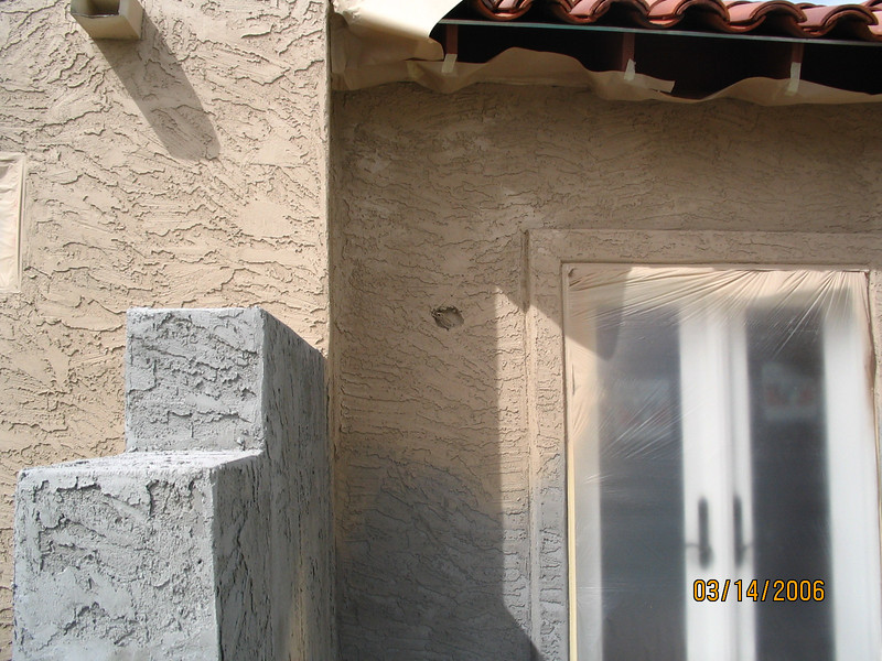 Spray-painted stucco at the master bedroom door.
