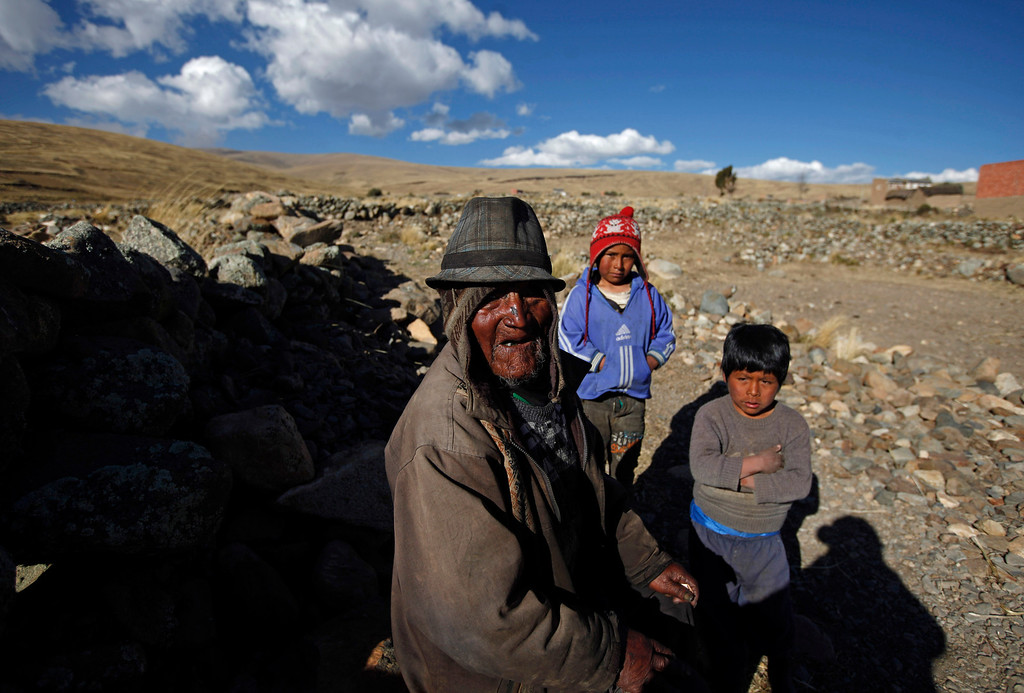 . Carmelo Flores Laura, a native Aymara, poses for a photo with his great-grandchildren outside his home in the village of Frasquia, Bolivia, Tuesday, Aug. 13, 2013.  If Bolivia�s public records are correct, Flores is the oldest living person ever documented. They say he turned 123 a month ago. Flores has 40 grandchildren and 19 great-grandchildren but most have left his hamlet of Frasquia, a dozen homes a two-hour walk from the nearest road in Warisata.  (AP Photo/Juan Karita)