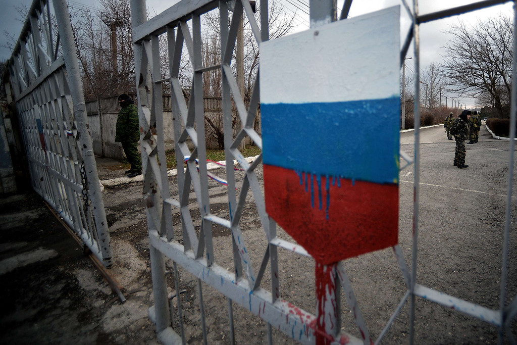 """. Members of the new pro-Russian forces dubbed the \""""military forces of the autonomous republic of Crimea\"""" stand at the gate, adorned with a Russian flag, of  Simferopol\'s republican military enlistment complex on March 10, 2014. Crimea\'s pro-Russian authorities sought to boost their claim to break from Ukraine Monday as volunteer soldiers swore an oath of allegiance in front of prime minister Sergei Aksyonov. He told journalists 186 volunteers had so far joined the new Crimean \""""self-defense\"""" units after pro-Moscow forces took power in the region and announced their intention to join with Russia, with a referendum planned for Sunday.     FILIPPO MONTEFORTE/AFP/Getty Images"""