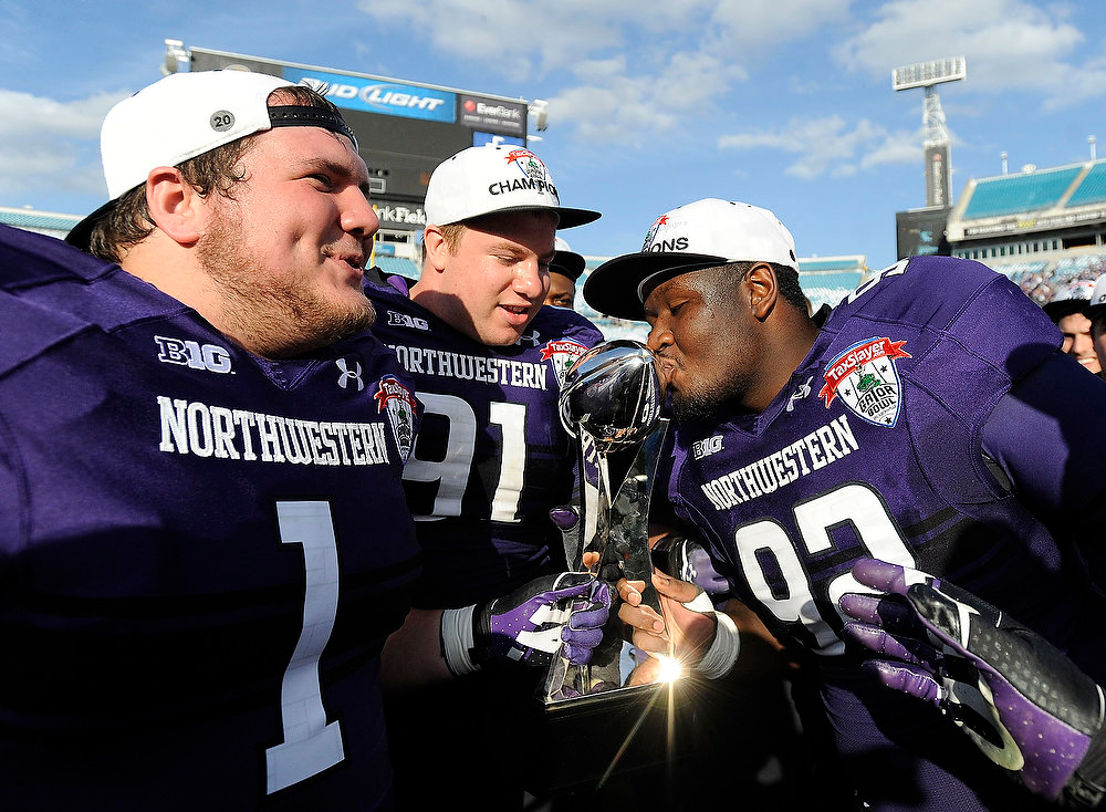 Description of . Northwestern defensive lineman Brian Arnfelt (91) and Bo Cisek (1) holds the trophy while their teammate Will Hampton (92) kisses it after the Gator Bowl NCAA college football game against Mississippi State, Tuesday, Jan. 1, 2013 in Jacksonville, Fla. Northwestern won 34-20.  (AP Photo/Stephen Morton)