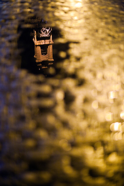 The bell tower of San Lorenzo church reflected on a puddle, Seville, Spain